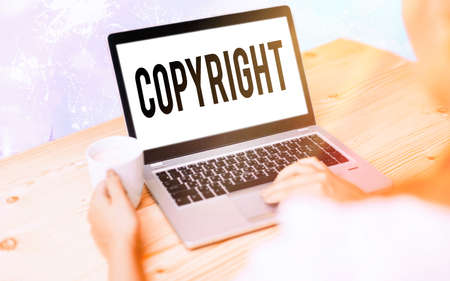 Conceptual hand writing showing Copyright. Concept meaning exclusive legal right to reproduce, publish, sell, or distribute Modern gadgets white screen under colorful bokeh background