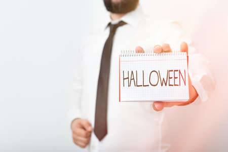 Handwriting text writing Halloween. Conceptual photo October 31 observed especially with dressing up in disguise Model displaying different empty color notepad mock-up for writing idea 版權商用圖片