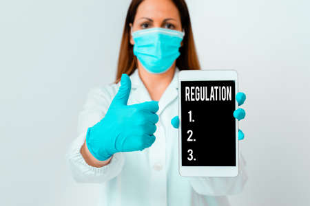 Conceptual hand writing showing Regulation. Concept meaning the authoritative rule dealing with details or procedure Laboratory technician featuring paper accessories smartphone