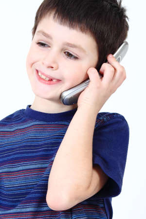 Small boy calling from mobile phone to friend on white background photo