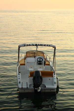 моторизованный: backside of small motorized boat with sunset