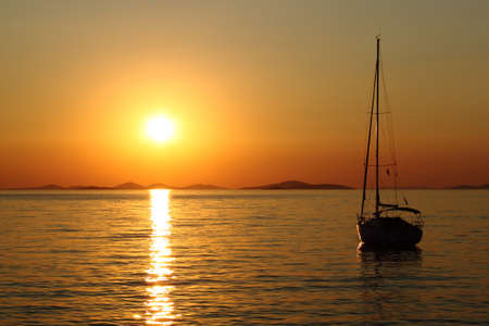 Gold romantic sunset with silhouette of yacht Stock Photo - 7435128