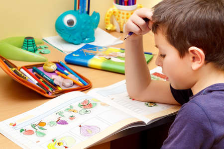 boy doing homework  with color pencil, painting fruits Standard-Bild