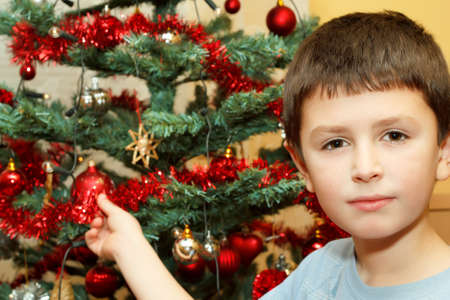 Young boy holding Christmas decorations on tree  photo