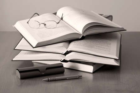 opened books pen and glasses on sepia background photo