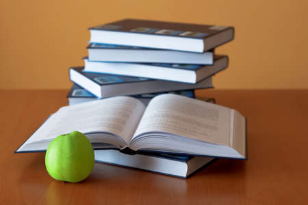 green apple and opened books on the desk Stock Photo - 8512574