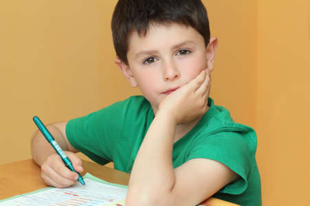 boy doing homework from school in workbook