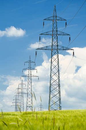 conductor electricity: high voltage power lines in field against a blue sky  Stock Photo