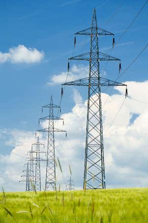 high voltage power lines in field against a blue sky  Standard-Bild