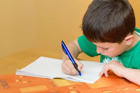 small school boy writting homework from school in workbook Standard-Bild