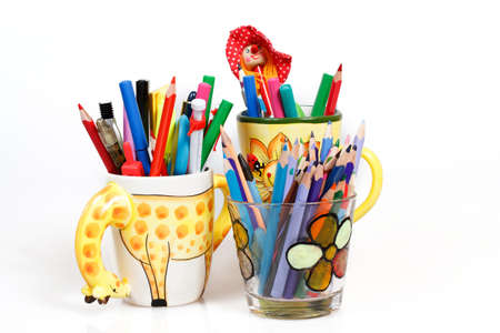 pen holders full of brightly colored pens on a white background  photo