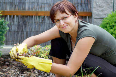 smiling middle age woman gardener with flowers outdoor in her garden  Stock Photo