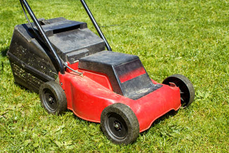 lawnmower on green grass in sunny day photo