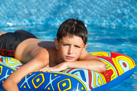 Boy with inflatable water lounger in the swimming pool Stock Photo - 14381706