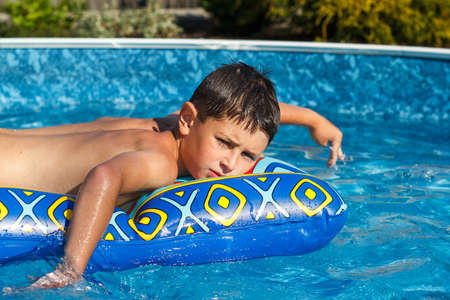 Boy with inflatable water lounger in the swimming pool photo