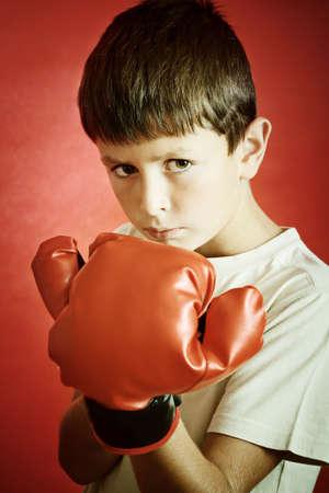 赤いボクシング用グローブと若い少年ボクサー