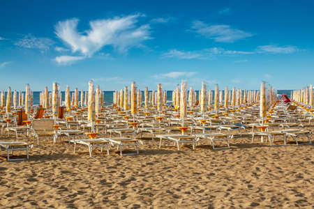 withdrawn yellow umbrellas and sunlongers on the sandy beach in Italy photo
