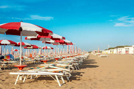 red and white umbrellas and sunlongers on the sandy beach in Italy photo