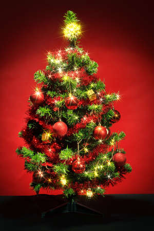 xmas tree: Decorated christmas tree with red balls on red background Stock Photo