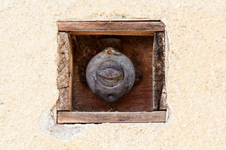 covered vintage retro light switch on house wall photo