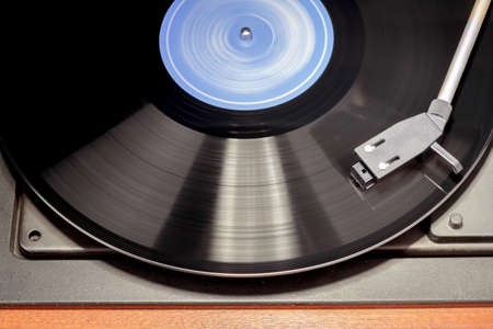 Detail of vintage record player with spinning vinyl. Motion blur image.