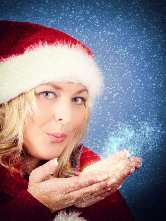 Joyful pretty woman blowing stars in red santa claus hat on snowy blue background photo