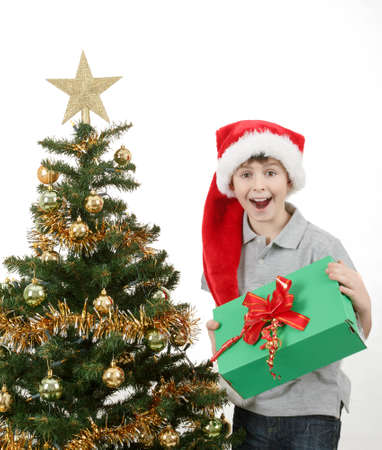 surprised boy in santa hat with christmas present on white background photo