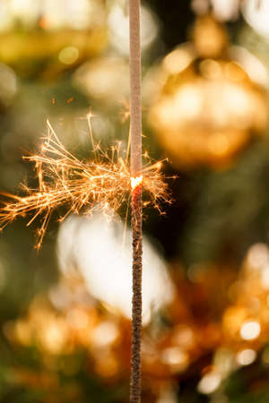 burning sparkler and out of focus christmas tree  photo