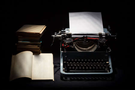 retro typewriter with stack of book and one opened book black background