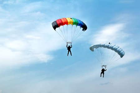 deux silhouettes de parachutistes non identifiés sur le ciel bleu