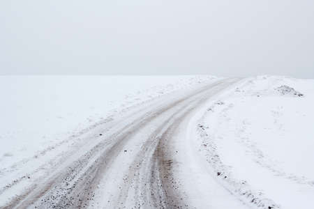 overcast winter landscape with rural road ending on horizon