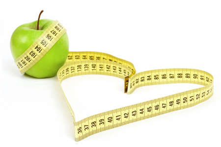 Tape measure heart shape and green apple  - health, weight concept
