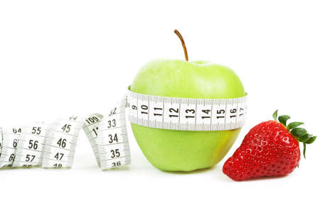 Measuring tape wrapped around a green apple and strawberry as a symbol of diet concept photo