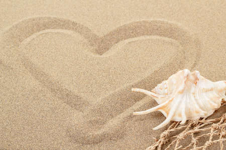 handwritten heart on yellow soft sand with seashell and shallow focus photo