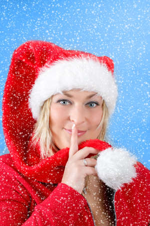 Joyful pretty woman in red santa claus hat smiling on blue background photo
