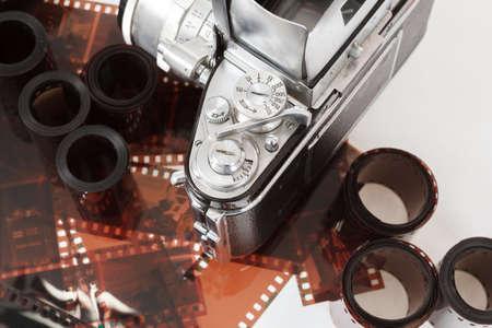 handled: analog vintage SLR camera and color negative films on white