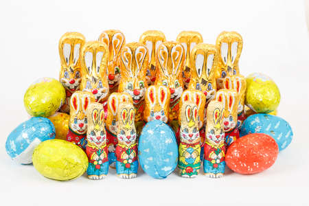 group of many color easter chocolate rabbits bunny and eggs on white background photo