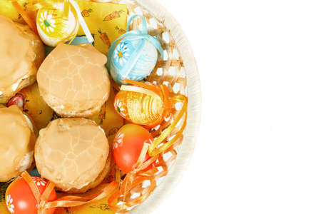 easter eggs and homemade sweet cakes in basket on white photo