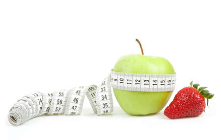 Measuring tape wrapped around a green apple and strawberry as a symbol of diet concept Stock Photo