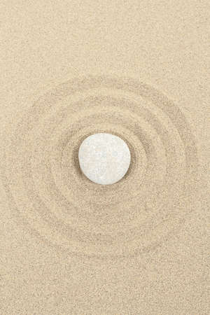 stacked up: zen stones in soft sand with circles Stock Photo