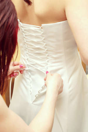closeup portrait of a maid of honor helping the bride with her dress