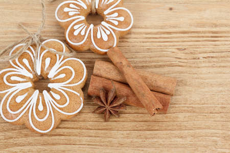 Gingerbread cookies hanging over wooden background with anise and cinamon photo