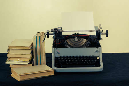 Old typewriter with paper and books, retro colors on the desk photo
