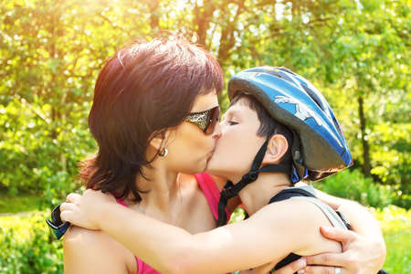 Mother kisses her son with bicycle helmet outdoor photo