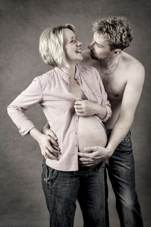 Loving happy couple, pregnant woman with her husband, toned, looking at each other photo