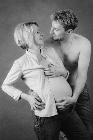 Loving happy couple, pregnant woman with her husband, black and white, looking at each other photo