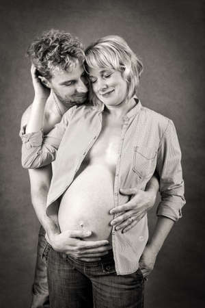 Loving happy couple, pregnant woman with her husband, black and white, romantic scene photo