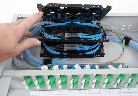 stack of fiber optic splice cassettes with protection sleeve and blue fibres installed in optical distribution frame photo