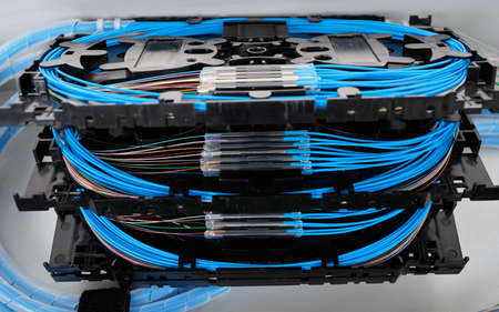 fibres: stack of fiber optic splice cassettes with protection sleeve and blue fibres installed in optical distribution frame Stock Photo