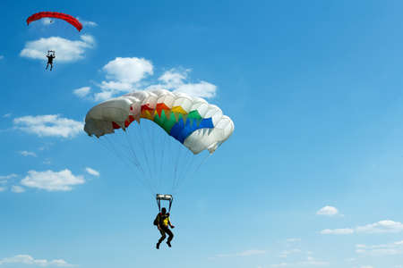 two silhouettes of unidentified skydivers on blue sky